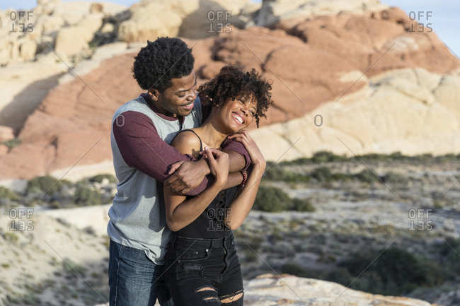 Romantic couple standing against rock formation