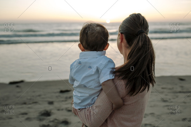 Side view of mother carrying son while standing at beach against sky during sunset