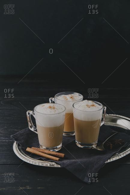Three chai lattes on a silver tray