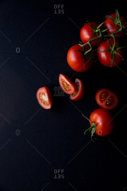 Top down view of whole and sliced vine tomatoes on black background