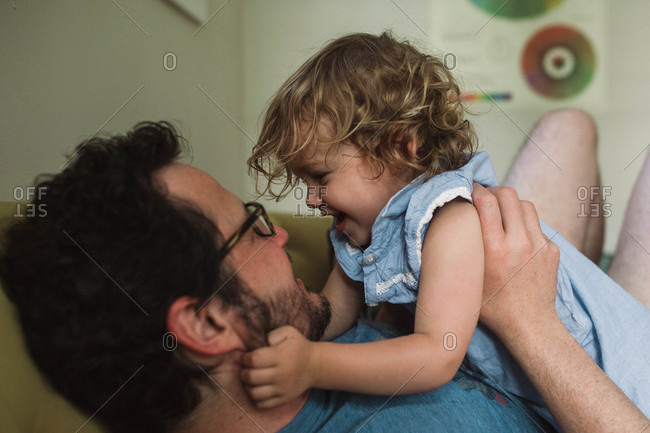 Little child grabbing dad's beard as they play on the couch