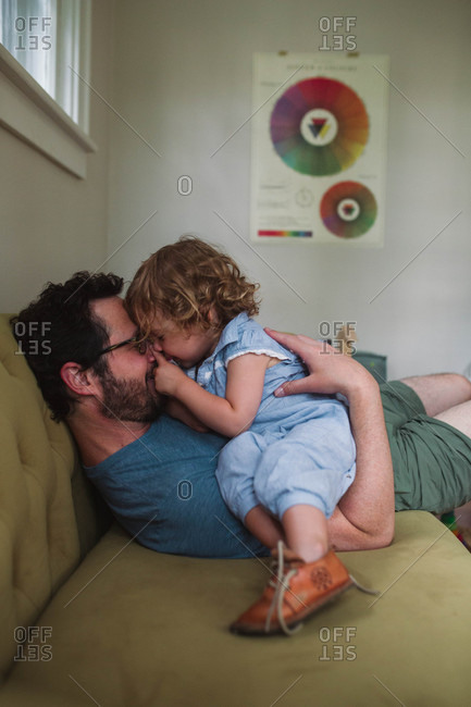 Small child giving dad eskimo kiss with his nose while hanging out on the couch together
