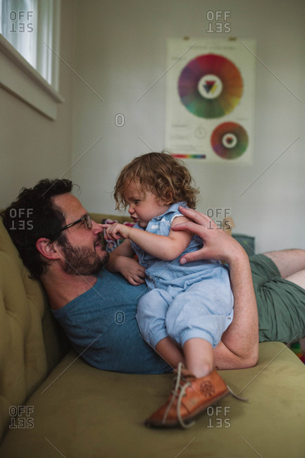 Small child poking dad on the nose while hanging out together on the couch