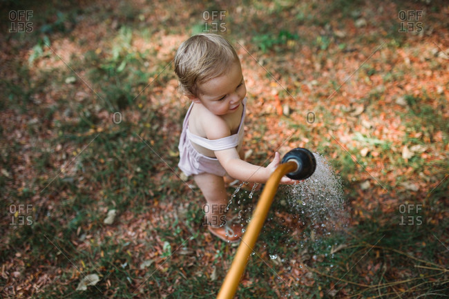 Toddler reaching hand out to touch spraying water from garden hose