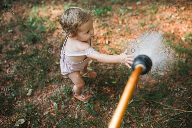 Little baby boy tentatively reaching for water spraying from garden hose