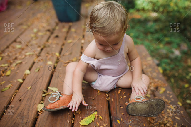 Curious toddler sitting on deck playing with fallen leaves