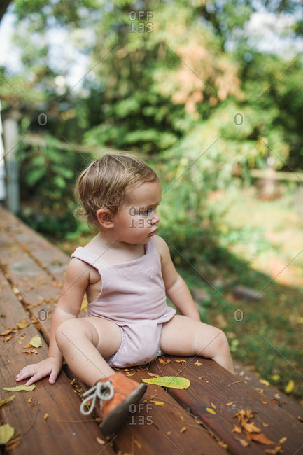 Toddler sitting on deck of house looking out at yard