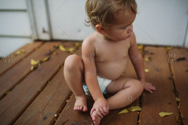 Toddler sitting on deck in diaper searching for something
