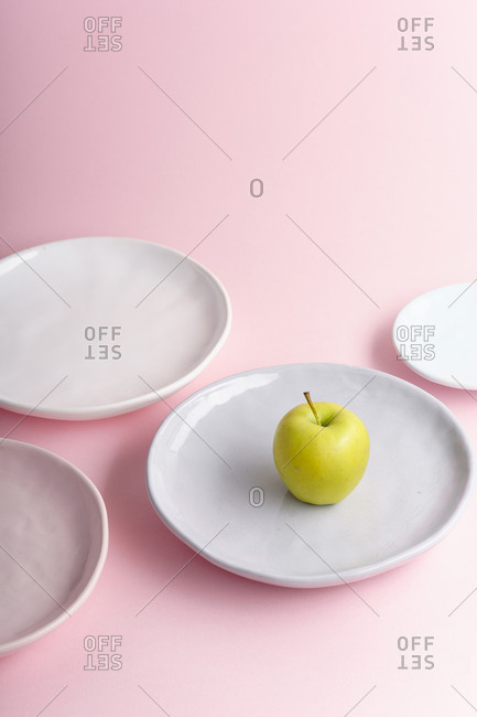 Collection of handcrafted ceramic plates on pink background