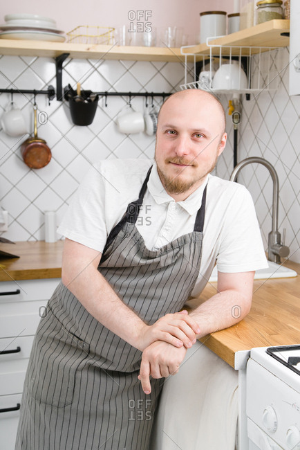 Young bald-headed man with mustache and beard posing at the home kitchen. Male cooking style concept