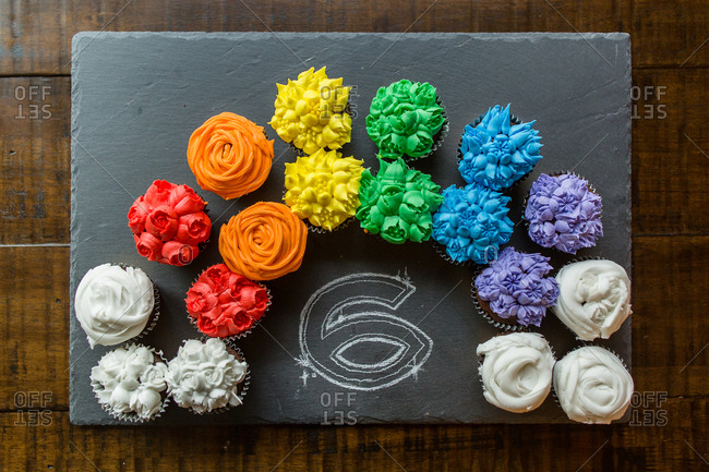Overhead view of colorful cupcakes arranged around number six on slate