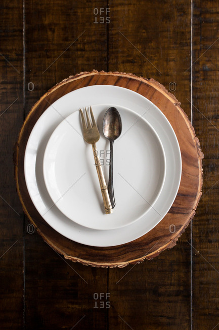 Top down view of antique spoon and fork arranged on empty plates