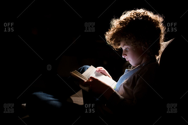 Young boy with curly hair illuminated by lamp light as he reads a book