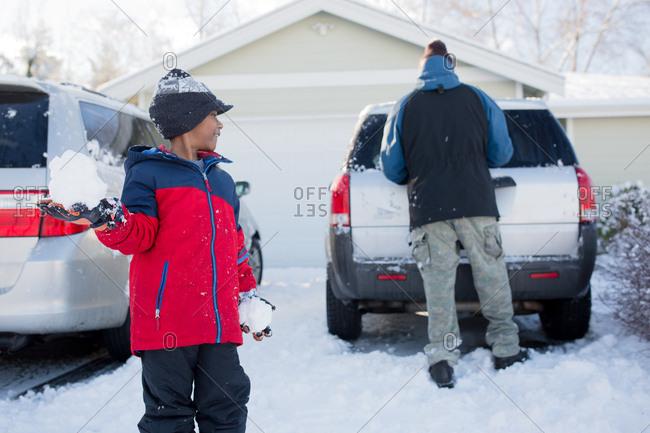 Young boy preparing to throw big snowball at dad's back