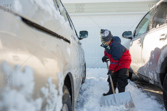 Young boy doing his chores by shoveling snow from between cars