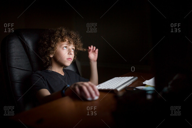 Young boy sitting in dark room lit by glow from computer screen