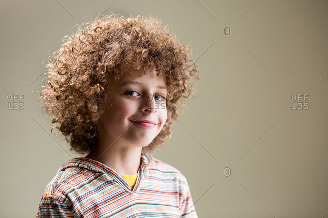 Studio portrait of young biracial boy smiling and looking at camera