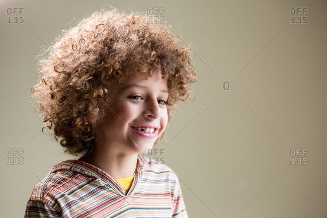 Portrait of young biracial boy in studio laughing and having fun