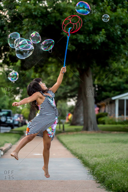 Young girl in jumping to catch bubbles floating in mid air