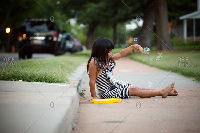 Young girl sitting on sidewalk playing with bubbles