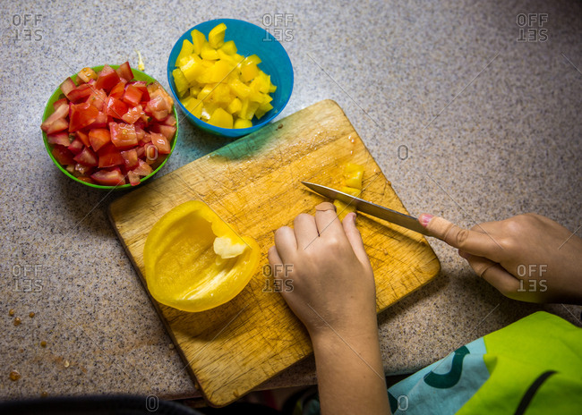 Top down view of child with bandage on finger dicing yellow capsicum on chopping board