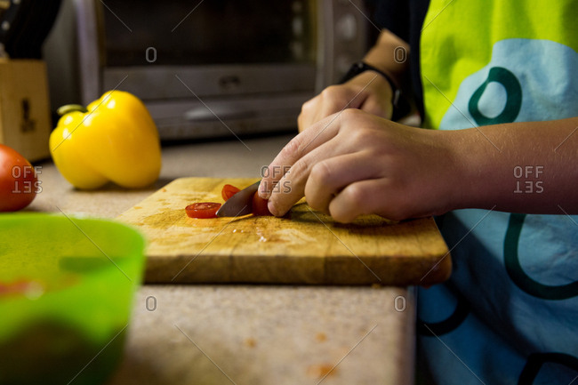 Low angle view of pair of children's hands slicing cherry tomatoes in kitchen