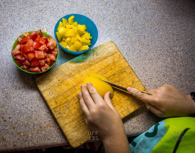 Overhead view of small pair of hands with bandage on finger slicing capsicum in kitchen