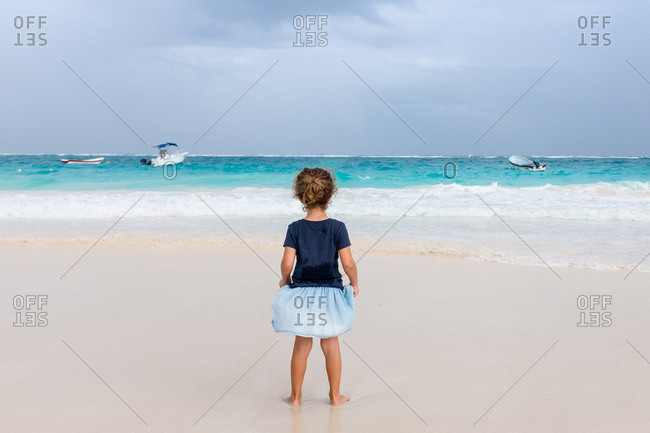Girl looking out over stormy ocean from the beach