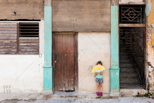 Girl holding a fan on the streets of Havana