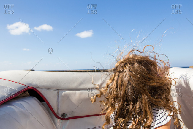 Girl with windswept hair in a convertible car