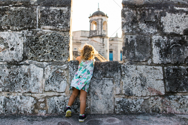 Girl looking through fortress walls in Havana, Cuba