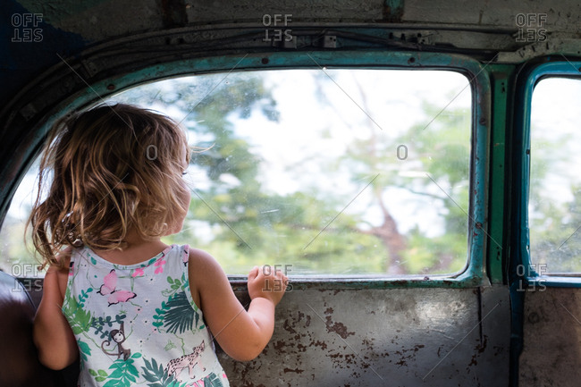 Young girl looking out the window of an old car in Cuba