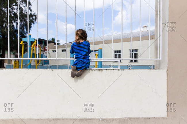 Girl on a wall, looking through a fence into a playground