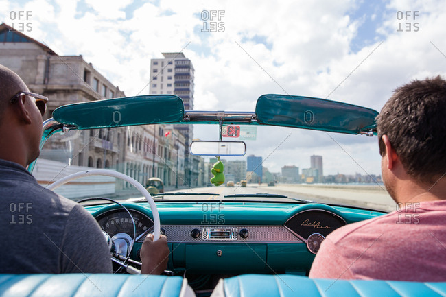 Havana, Cuba - November 19, 2016: Men riding in the front seat of a convertible down the Malecon