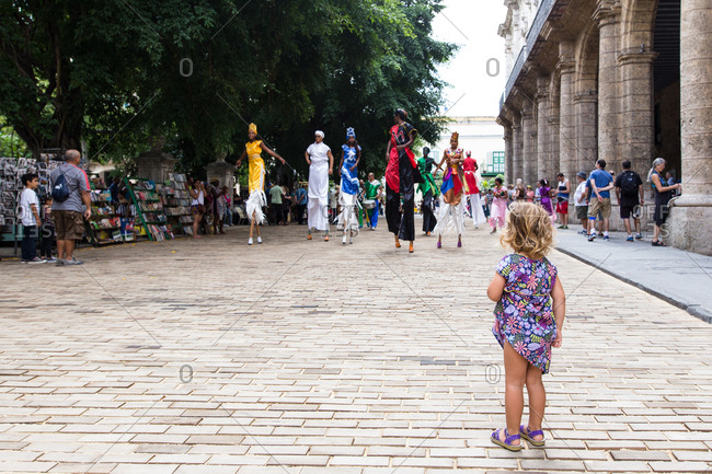 Havana, Cuba - November 19, 2016: Girl watching street performers at Plaza de Armas