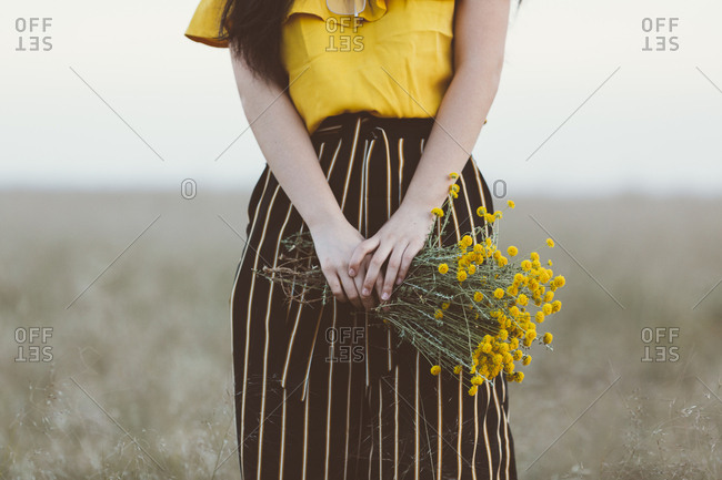 Woman in field holding yellow flowers