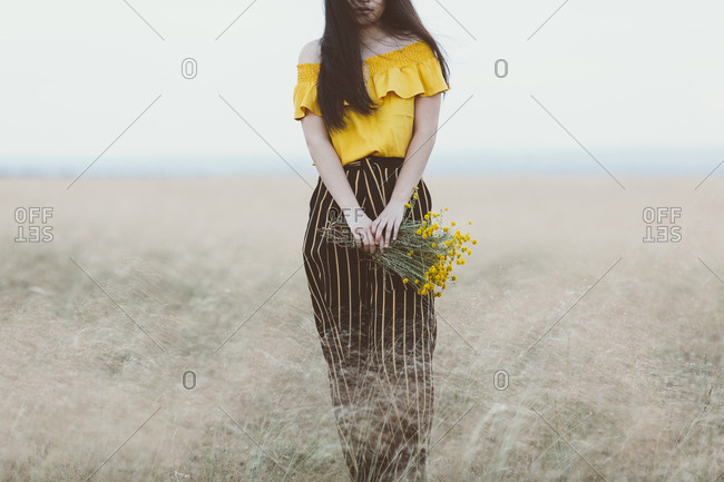 Young Asian woman in field holding yellow flowers