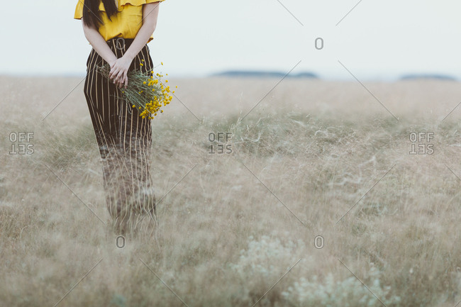 Young woman in field holding yellow flowers