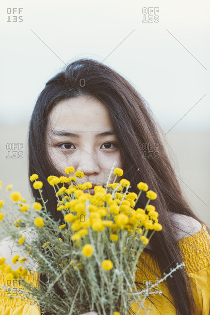 Asian woman in field holding yellow flowers