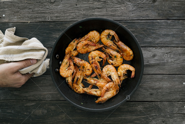 Hand holding pan with cooked seafood