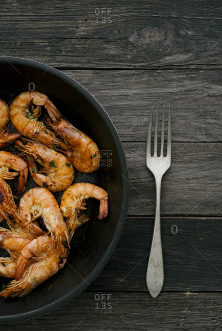 Pan with cooked seafood and fork