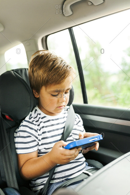 Little boy playing video game while riding in care