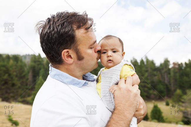 Father kissing baby's cheek outdoors