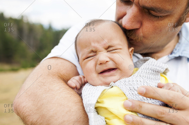 Father kissing upset baby outdoors