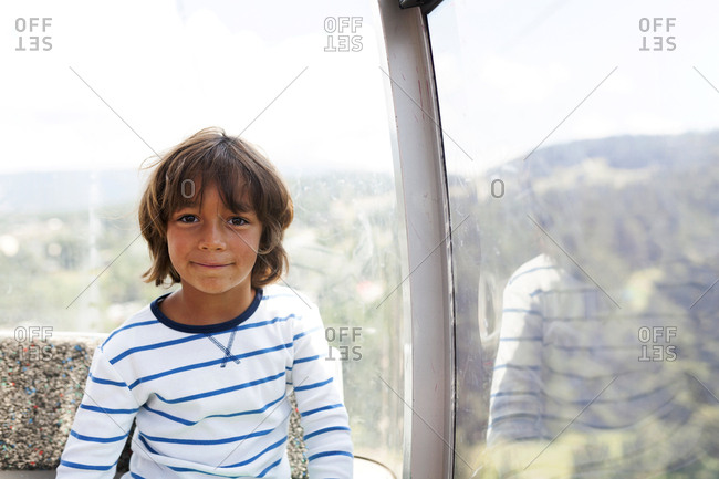 Portrait of smiling boy sitting by window in observation wheel