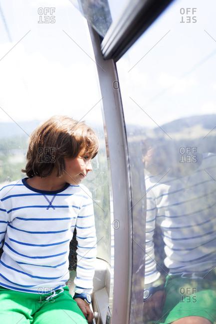 Little boy looking out window of observation wheel