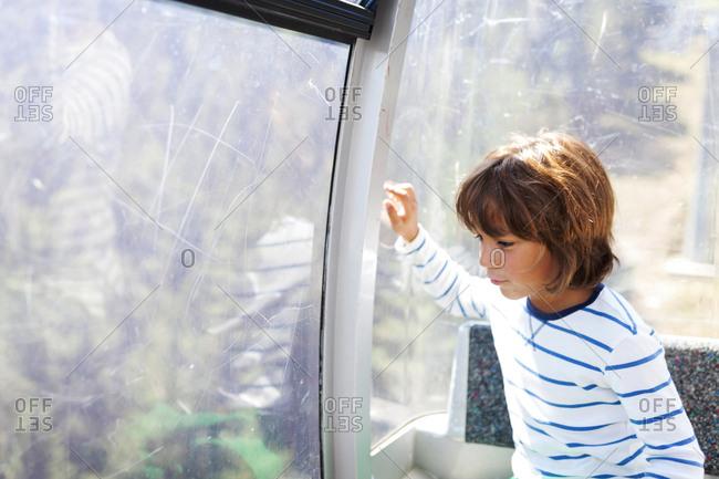 Boy looking out window of observation wheel