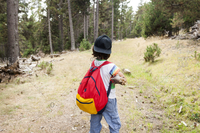 Rear view of child hiking with red backpack