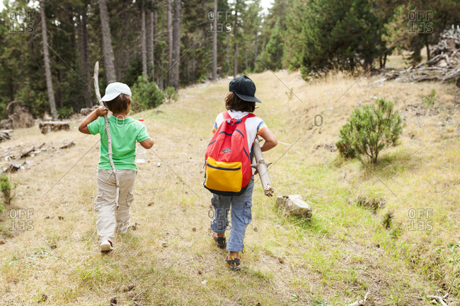 Rear view of two kids hiking with sticks