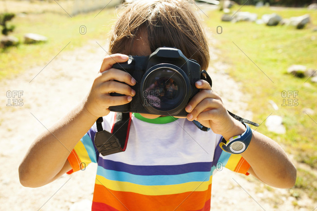 Young boy holding camera
